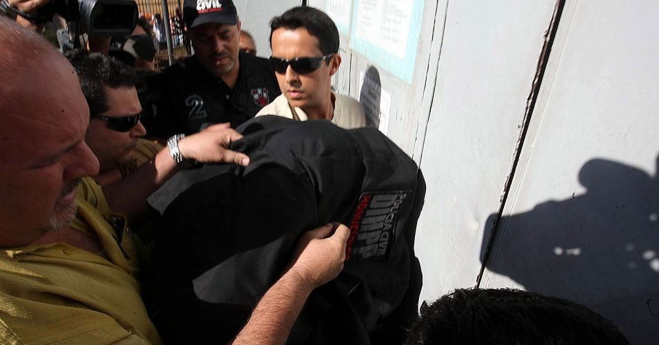 Menor envolvido no caso (sob casaco preto) é transportado pelos policiais na tarde desta quinta-feira (8) no Departamento de Investigações de Belo Horizonte