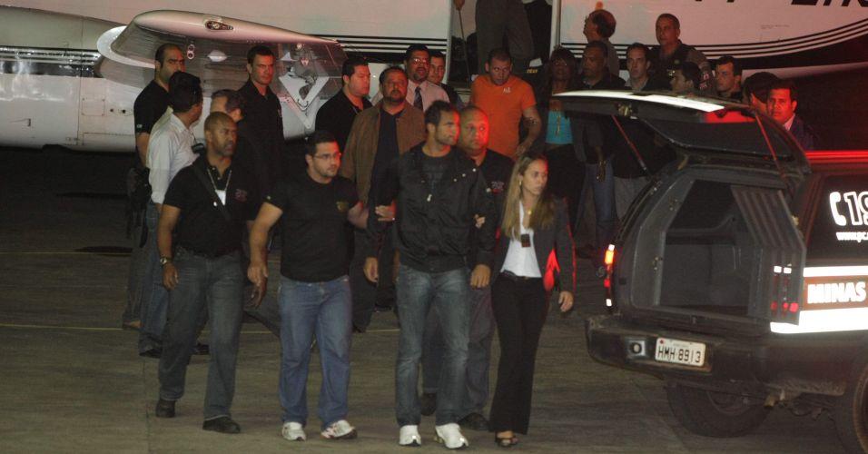 O goleiro Bruno (ao centro) e o seu amigo Luiz Henrique Ferreira Romão, o Macarrão (de laranja, ao fundo), ao chegarem ao aeroporto de Pampulha, em Belo Horizonte (MG), na noite desta quinta-feira. A Justiça do Rio determinou a transferência atendendo a uma solicitação da Justiça mineira