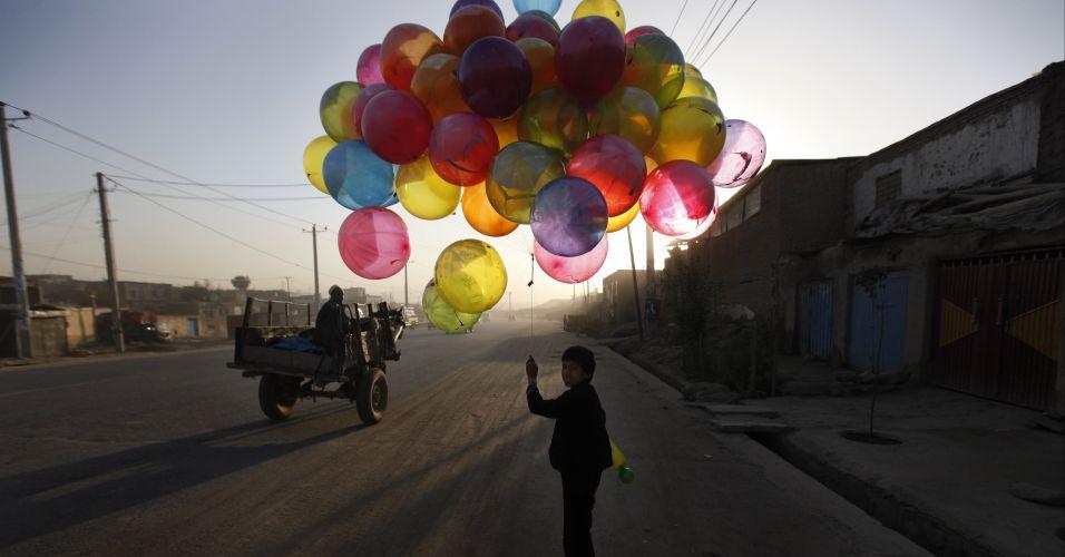 Criança vende balões no Afeganistão