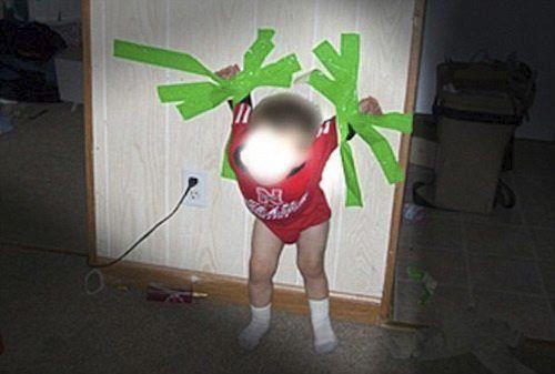 Criança pregada na parede