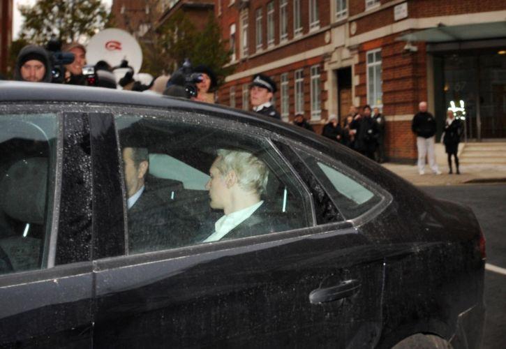 O fundador do WikiLeaks, Julian Assange (cabelos claros), chega à cortede Westminster acompanhado de seus advogados após se apresentar voluntariamente à uma delegacia de polícia em Londres na manhã desta terça-feira (7)