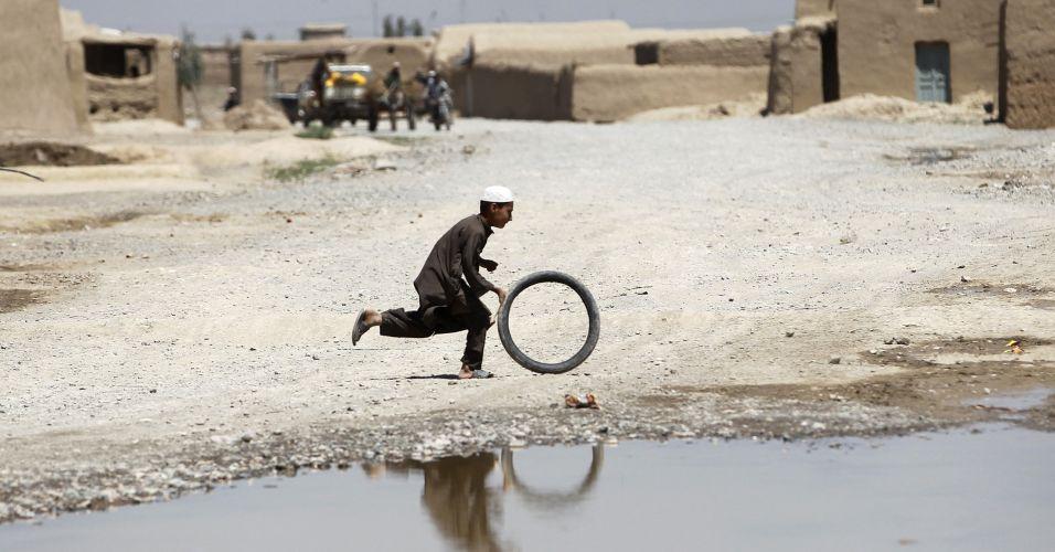 Menino brinca com pneu