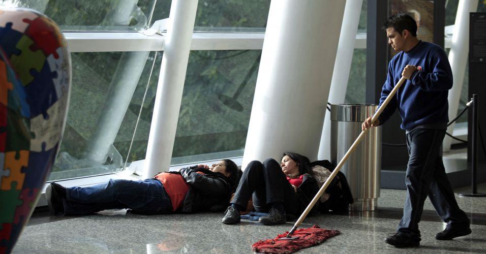 09.jun.2011 - Duas mulheres dormem no chão do aeroporto Jorge Newbery, em Buenos Aires, na Argentina. Todos os voos foram cancelados na capital argentina na tarde de quinta-feira devido à nuvem de cinzas do vulcão chileno Puyehue