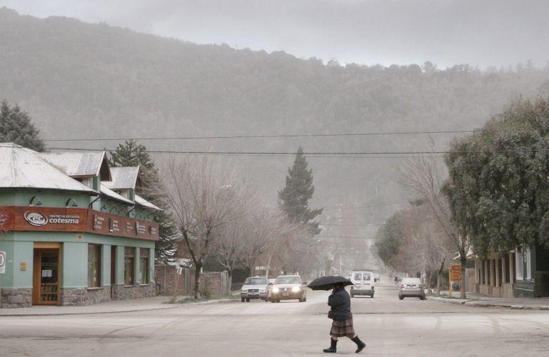 12.jun.2011 - Mulher atravessa rua coberta por cinzas de vulcão em San Martin de Los Andes, na Patagônia, Argentina
