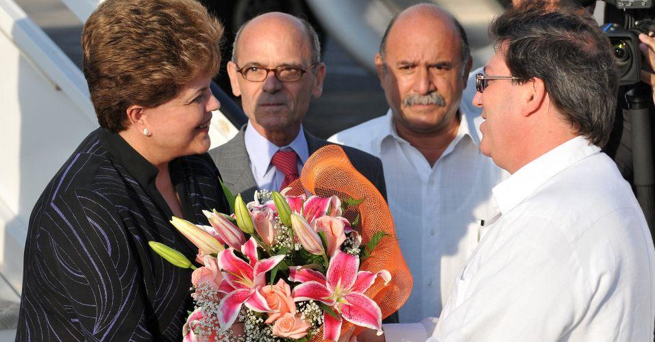 30.jan.2012 - Presidente Dilma Rousseff é recebida pelo ministro de Relações Exteriores de Cuba, Bruno Rodríguez, nesta segunda (30), em Havana. Esta é a primeira visita oficial da presidente ao país, onde se reunirá com Raúl Castro para avaliações de relações bilaterais econômicas