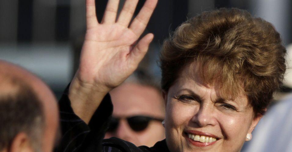 30.jan.2012 - Presidente Dilma Rousseff acena para os cubanos que foram recepcioná-la em sua chegada ao país na noite desta segunda-feira (30). Esta é a primeira visita oficial da presidente a Cuba, onde se reunirá com Raúl Castro para avaliações de relações bilaterais econômicas